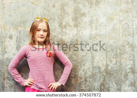 Fashion portrait of a cute little girl of 8 years old, wearing red and grey t-shirt - stock photo