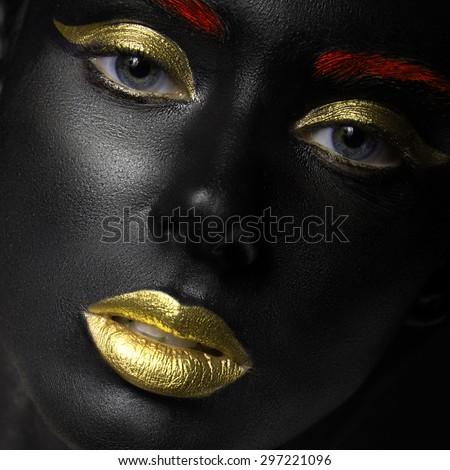 fashion portrait of a dark-skinned girl with color make-up.Beauty face. Picture taken in the studio on a black background. - stock photo