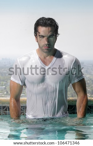 Fashion portrait of a gorgeous male model in soaked wet t-shirt standing in luxurious swimming pool with city background - stock photo