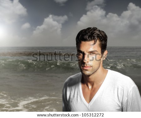 Fashion portrait of a handsome man against ocean background - stock photo