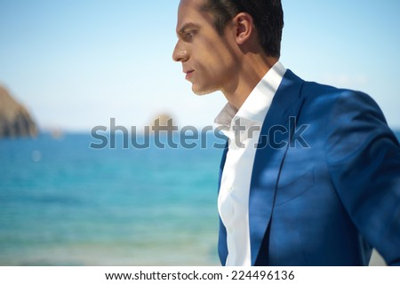 Fashion portrait of a handsome man in blue suit - stock photo