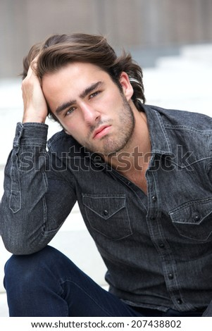 Fashion portrait of a handsome young man sitting with hand in hair