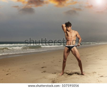 Fashion portrait of a muscular toned male model on beautiful beach - stock photo