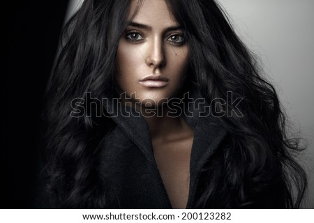 Fashion portrait of a sensual brunette girl with curly long black hair. - stock photo