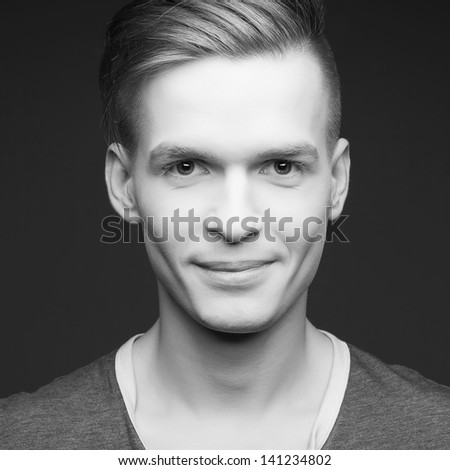Fashion portrait of a smiling elegant young and handsome man posing over gray background. Perfect skin and hair. Close up. Black and white (monochrome) studio shot - stock photo