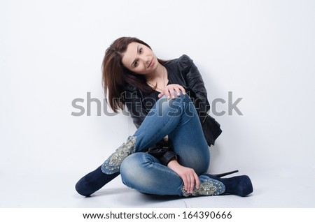 fashion portrait of a young girl at a wall - stock photo