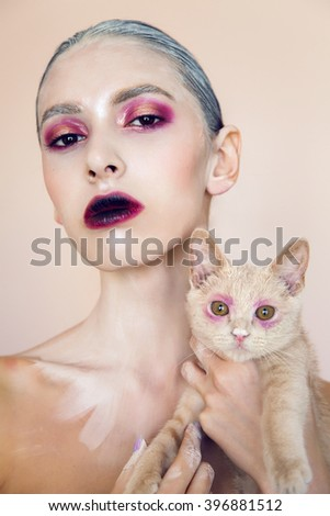 fashion portrait of a young girl in the Studio with paint on her face and with cat - stock photo