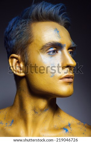 Fashion portrait of a young man with artistic make-up