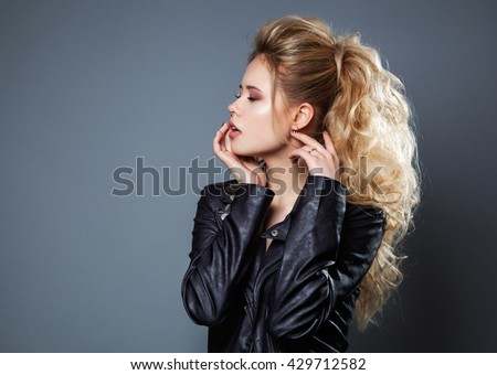 Fashion Portrait of attractive long hair blond young woman in black leather jacket over grey background. Studio shoot. Hairstyle. - stock photo