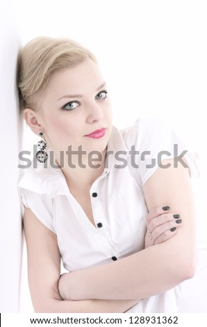 Fashion portrait of attractive woman with crossed arms dressed in the white blouse leaning against white wall - stock photo
