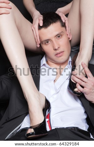 Fashion portrait of attractive young man embracing woman's perfect legs