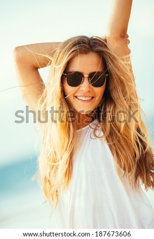 Fashion portrait of beautiful blond girl in sunglasses, wind fluttering her hair. Beach fashion lifestyle. - stock photo