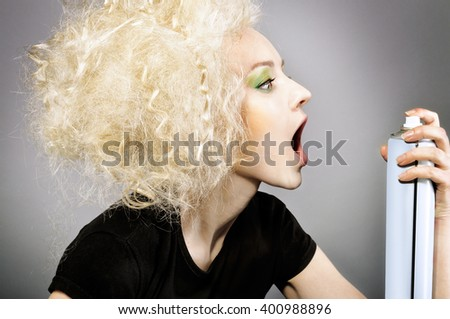 Fashion portrait of beautiful blonde woman with creative hairstyle. Funny or silly face expression with open mouth profile, holding hair spray bottle. - stock photo