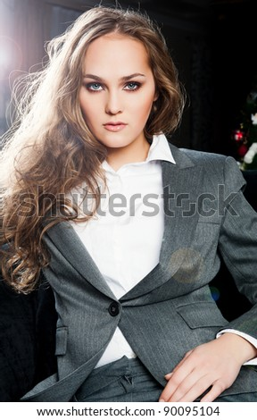 Fashion Portrait of beautiful business woman wearing luxury suit sitting relaxed and looking at camera - stock photo