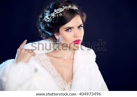 Fashion portrait of beautiful girl model in white fur coat with expensive jewelry, makeup and wedding hairstyle isolated on black background. - stock photo