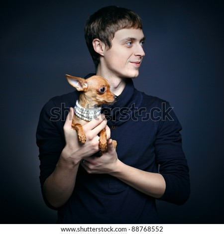 Fashion portrait of beautiful man with small dog - stock photo