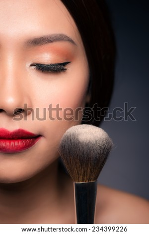 fashion portrait of beautiful sensual girl with bright makeup and tanned skin. Beautiful woman applying powder at party. Asian woman getting ready putting makeup on face.  - stock photo