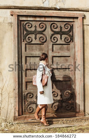 Fashion portrait of beautiful woman on the front of old vintage building