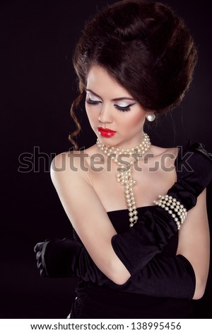 Fashion portrait of beautiful woman with pearl necklace on the bared shoulders over dark - stock photo