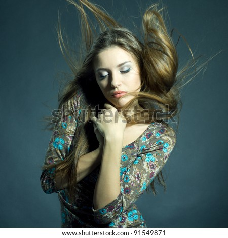 Fashion portrait of beautiful woman with streaming hair and closed eyes wearing bright jacket