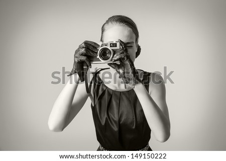 Fashion portrait of beautiful young girl in classic vintage style with an analogue photo camera - stock photo