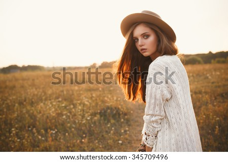 Fashion portrait of beautiful young pretty girl with hippie outfit and hat outdoors at sunset. Soft warm color tone. Boho lifestyle. Bohemian Style. Horizontal with blank space for text - stock photo