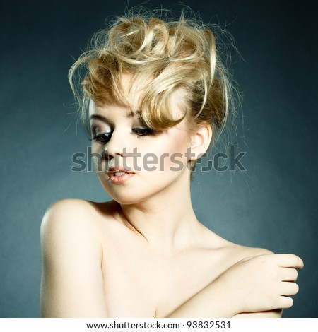 Fashion portrait of beautiful young woman posing on black background with modern styled hair - stock photo