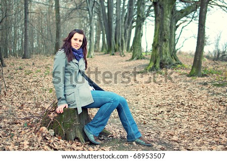 fashion portrait of beautiful young woman sitting on stump in the forest