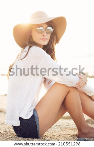 Fashion portrait of beautiful young woman wearing sunglasses and hat on the beach, bright warm sunny backlit color tone  - stock photo