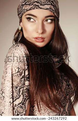 Fashion portrait of beautifull oriental woman with long dark hair bringth make up wearing shawl with snake print and gold earing - stock photo