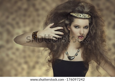 fashion portrait of cute brunette girl with curly hair-style, cute make-up and leopard accessories  - stock photo