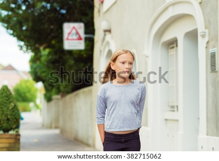 Fashion portrait of cute little girl of 7-8 years old, walking down the street, wearing grey top, toned image - stock photo