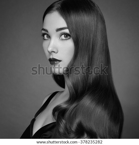 Fashion portrait of elegant woman with magnificent hair. Brunette girl. Perfect make-up. Girl in black dress. Curly hair. Black and white - stock photo
