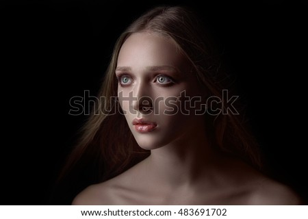 Fashion portrait of gorgeous young blond woman in studio on black