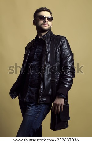 Fashion portrait of handsome  athletic young man with in trendy casual leather jacket,  jeans, trendy sunglasses and leather bag over yellow background. - stock photo