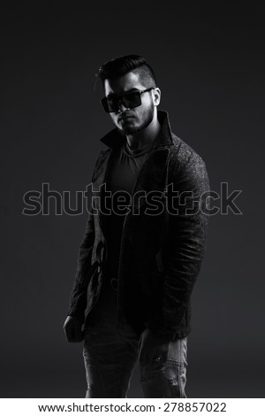 Fashion portrait of handsome stylish man in elegant jacket and glasses. Black and white image
