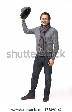 Fashion portrait of handsome young man in a sweater putting on his hat isolated on white background
