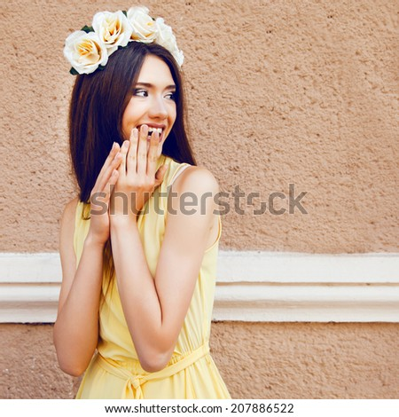 Fashion portrait of happy playful pretty brunette girl smiling and having fun, wearing pastel yellow dress and roses wreath. - stock photo