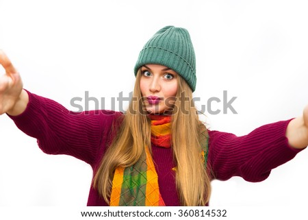 fashion Portrait of happy pretty teen girl making selfie. Winter outwear, trendy scarf, green hat and red sweater.Natural make up, posing against white wall.young traveler,hipster style.Sending kisses - stock photo