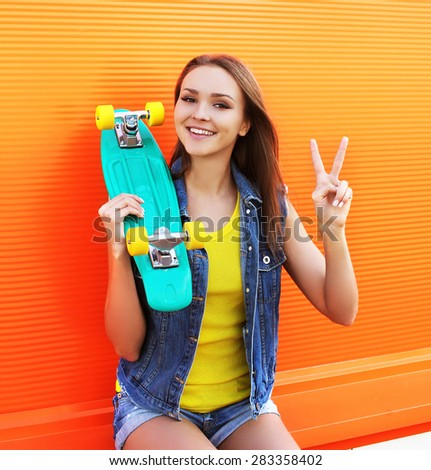 Fashion portrait of hipster cool girl in colorful clothes with skateboard having fun against the orange wall - stock photo
