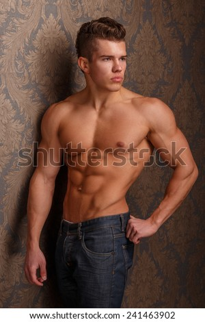 Fashion portrait of man showing his muscular body and poses over wall