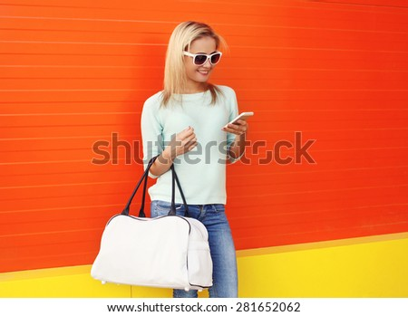 Fashion portrait of pretty smiling woman in sunglasses with bag using smartphone against the colorful orange wall - stock photo