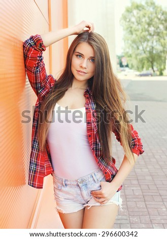 Fashion portrait of pretty woman model in checkered shirt with long hair outdoors - stock photo
