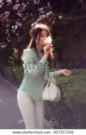 Fashion portrait of pretty woman wearing sexy white pants and turquoise polka dots shirt smelling magnolia posing outdoor - stock photo