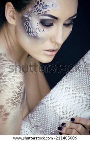 fashion portrait of pretty young woman with creative snake make up, fashion victim with python skin clutch. face like bag - stock photo