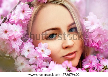 Fashion portrait of sexual beauty blonde in blooming pink flowers. Spring time