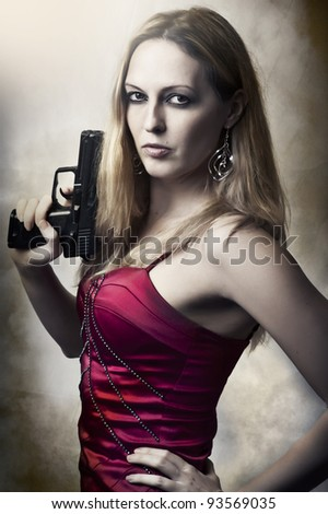 Fashion portrait of sexy dangerous woman holding gun