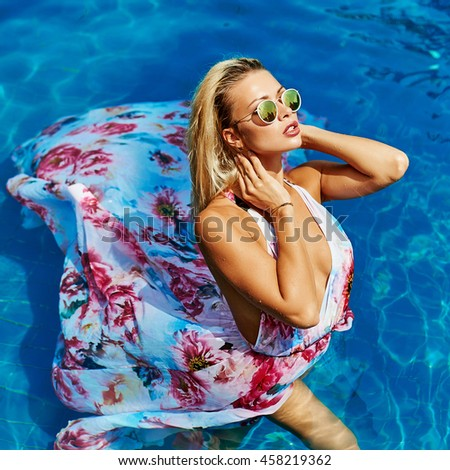 Fashion portrait of sexy female model posing in the pool