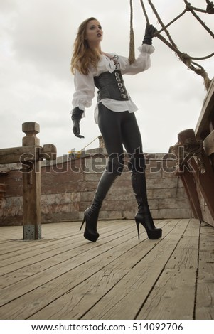 Fashion portrait of sexy woman in pirate style with old handgun at ship