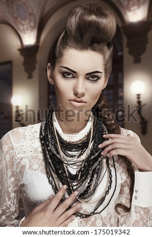 fashion portrait of sexy young brunette woman with amazing creative style, original hair-style and pretty make-up. Wearing white lace shirt and a lot of necklaces - stock photo